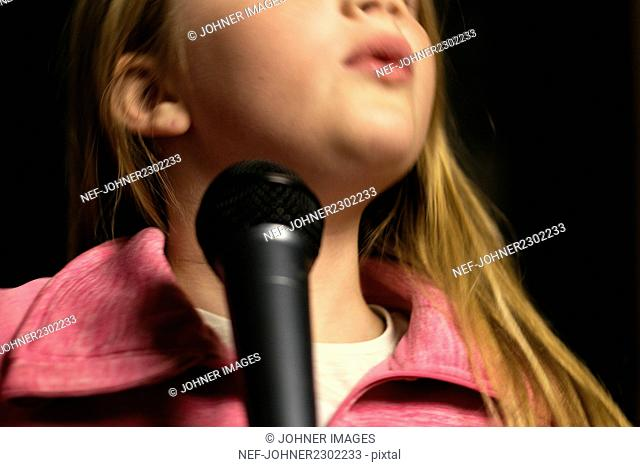Girl holding microphone and singing