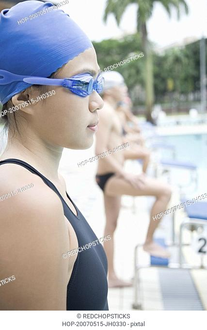 Side profile of a young woman wearing swimming goggles and standing at a poolside