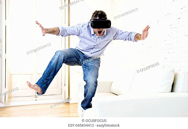 young modern man standing on sofa couch excited using 3d goggles watching 360 virtual reality vision enjoying the fun cyber experience in vr simulation reality...