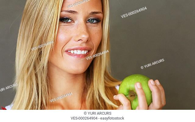 Closeup of a pretty young blond woman biting into an apple and having a giggle