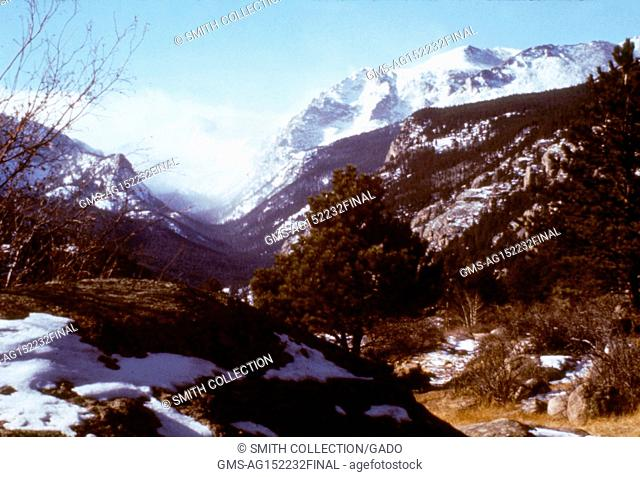 A photograph of Estes Park, Colorado, including a snow-covered mountain range, a valley with sparse snow, and several trees, 1975. Image courtesy CDC