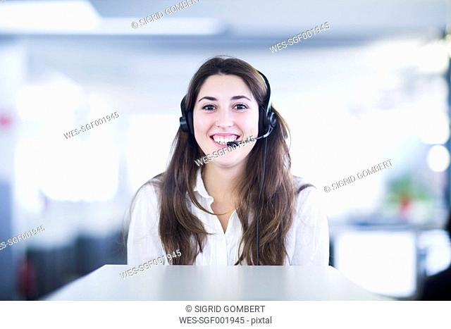 Portrait of smiling young woman with headset in an office