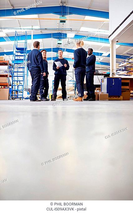 Surface level view of manager explaining to team in manufacturing factory