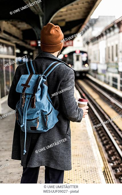 Young man waiting at metro station platform, holding disposable cup