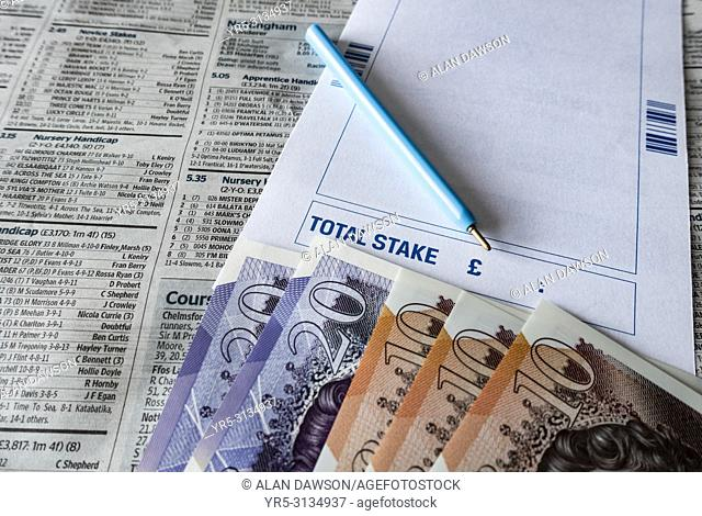 Betting slip and ten and twenty pound notes on horse racing page of newspaper in Betting shop in England. United Kingdom