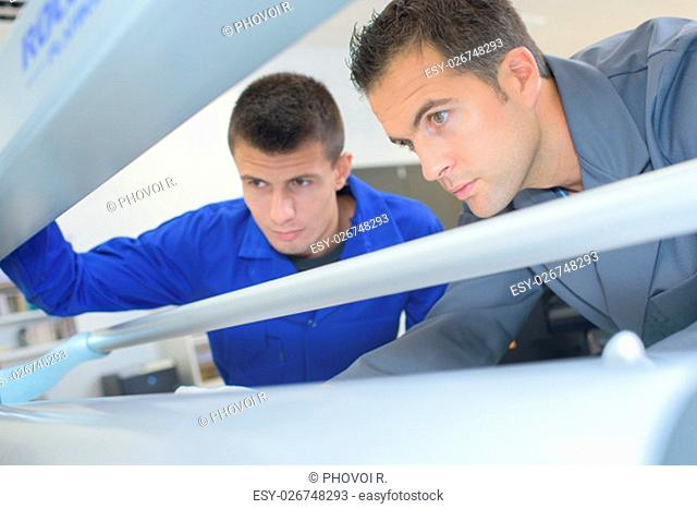 Two men looking into printing machine