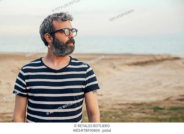 Portrait of bearded man on the beach looking at distance