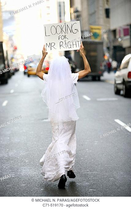 Bride in wedding dress running down street with back to camera holding a sign overhead reading 'Looking for Mr. Right'