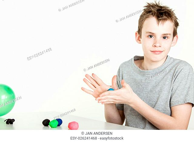 Happy young caucasian male child creating objects from various colored balls of clay on table with gray background