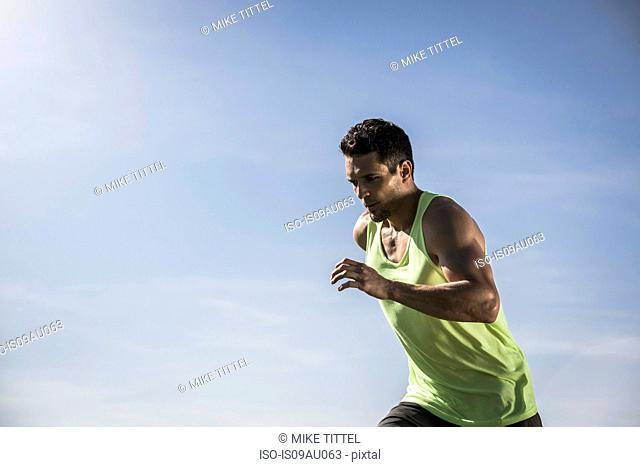 Young man wearing vest running in front of blue sky