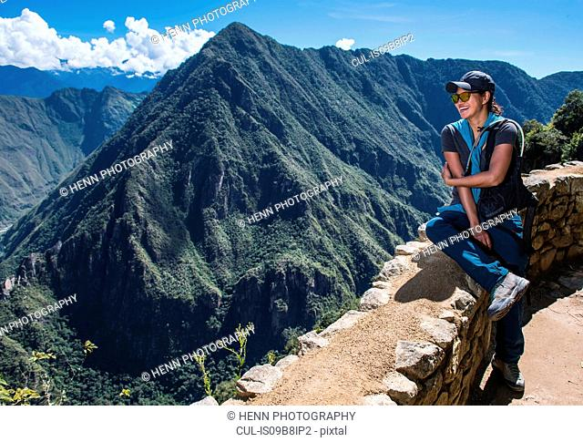 Woman resting on drywall on the Inca Trail close to Machu Picchu, Cusco, Peru