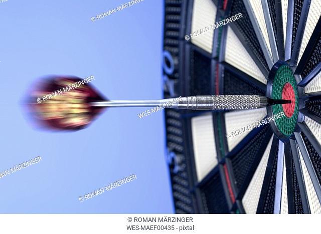 Dart Hitting Bullseye on Dartboard