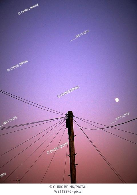 Telephone pole and wiring at dusk with moon in the UK