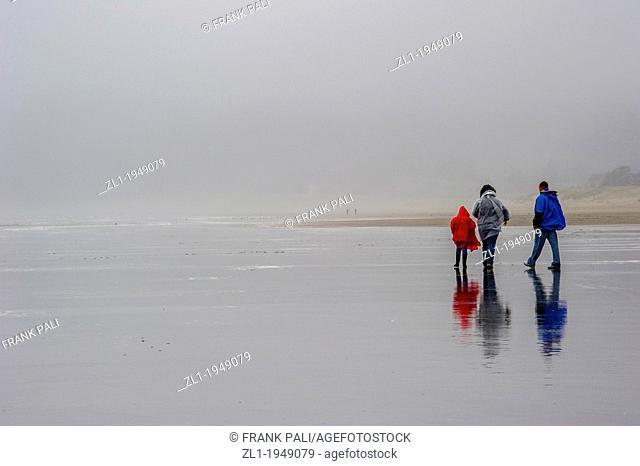 Family walking on rainy day on Cannon Beach.Cannon Beach,Oregon USA