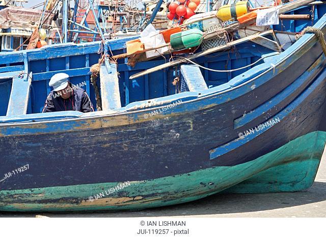 Fisherman working in fishing boat in Essaouira harbour, Morocco