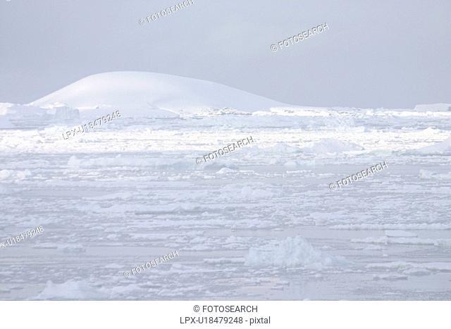 View across snow fields, tabular icebergs Antarctica Peninsula
