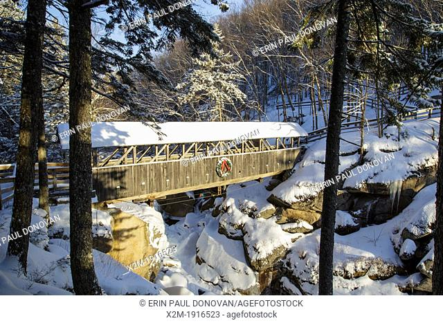 Franconia Notch State Park - Sentinel Pine Covered Bridge during the winter months  It is a footbridge which crosses over the Pemigewasset River in Lincoln