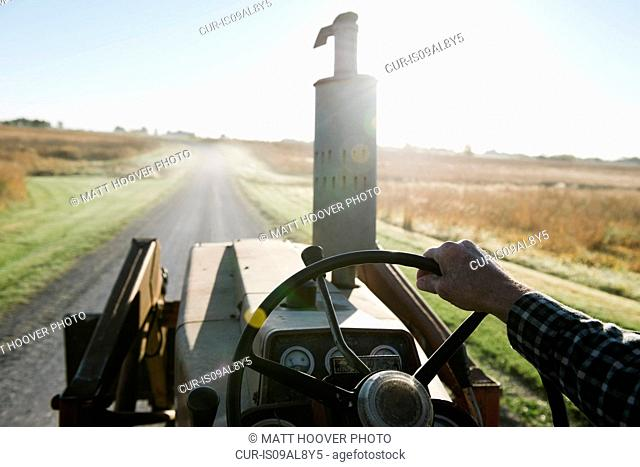Over shoulder view of senior male farmer driving tractor on rural road, Plattsburg, Missouri, USA