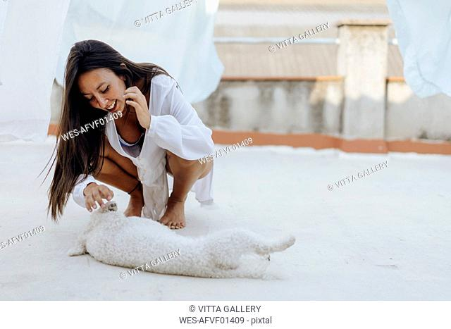 Happy young woman playing with her dog on roof terrace