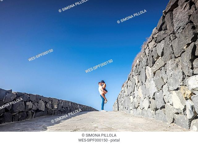 Spain, Tenerife, young couple in love in front of blue sky