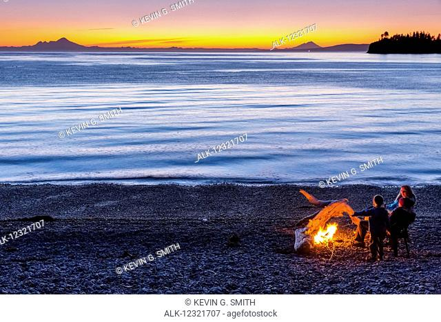 People enjoying a campfire on the beach at sunset, Hesketh Island, Southcentral Alaska, USA