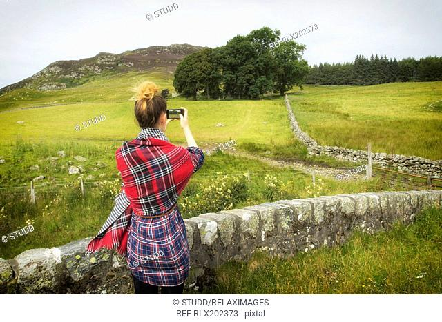 Rear view of teenage girl photographing grassy field