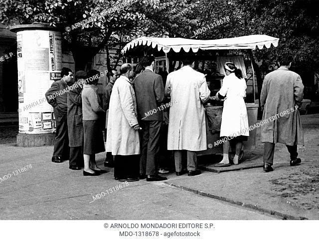 A pastry cook's kiosk in Sofia. Some Bulgarian citizens crowd around the kiosk of an itinerant pastry-cook. Sofia, November 1961