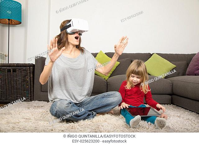 woman astonished with virtual reality, or 360, glasses, and three years old child using and watching digital tablet, sitting on carpet indoor home