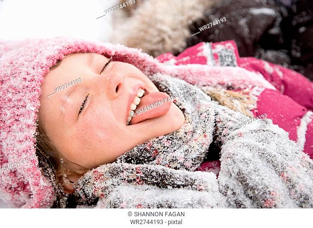 Girl in snow sticking out tongue