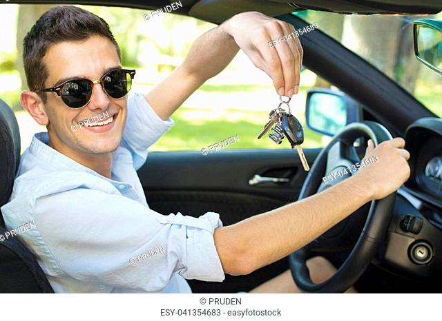 man with the keys to the car smiling behind the wheel