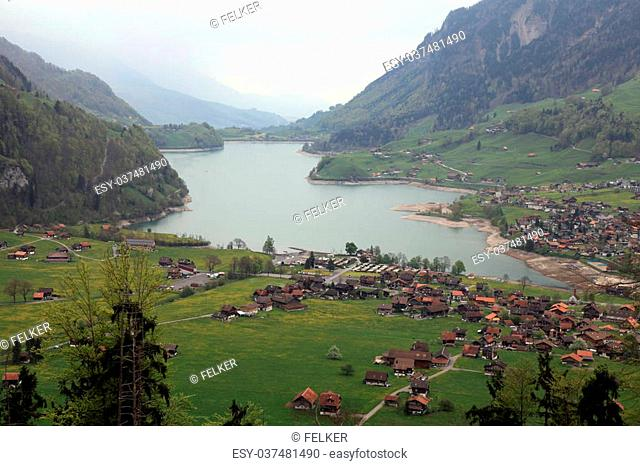Swiss alpine lake, mountains and village (Switzerland). Aerial view