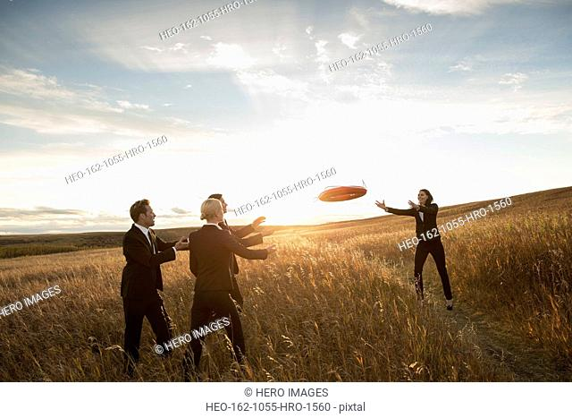 Businesswoman throwing buoy towards colleagues in field