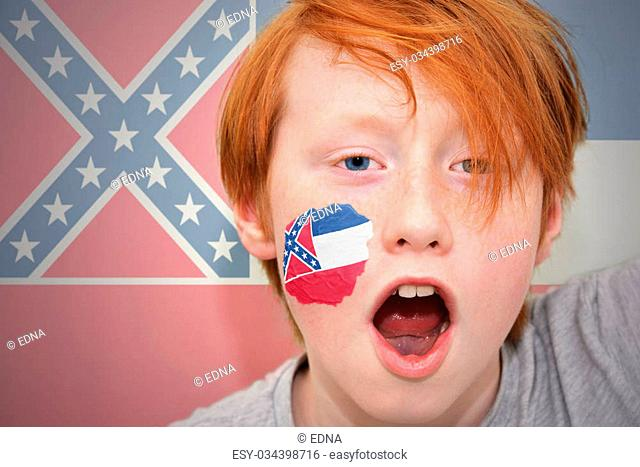 redhead fan boy with mississippi state flag painted on his face. on the mississippi state flag background
