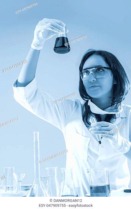 Female Laboratory Staff Dealing with Flasks During Scientific Experiment in Laboratory. Vertical Image Composition