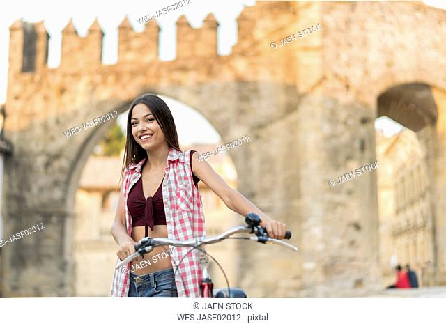Spain, Baeza, portrait of smiling young woman with bicycle in the city