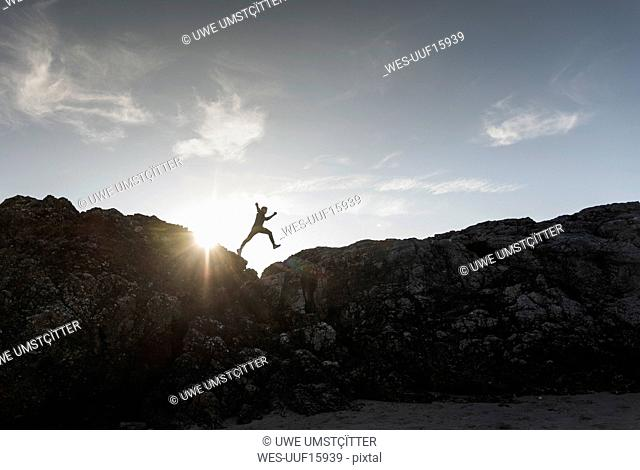 France, Brittany, young man jumping on a rock at sunset