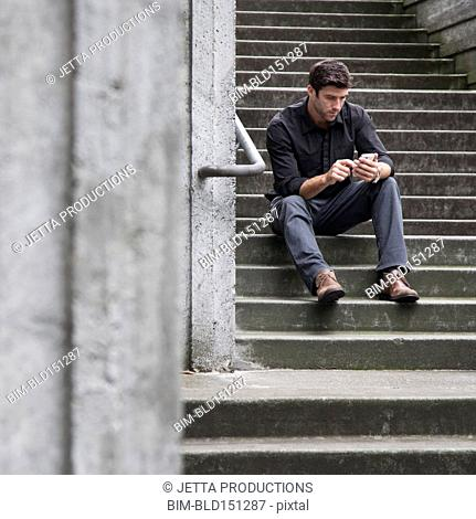 Caucasian businessman using cell phone on staircase outdoors