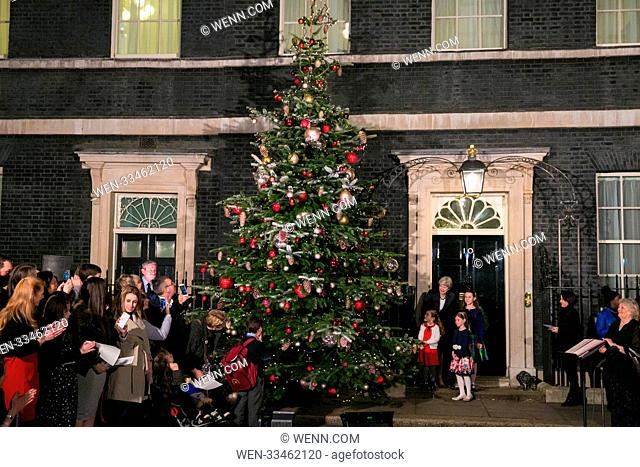 British Prime Minister Theresa May along with Emily Wood, Lilly Bo Morgan and Sophie Vysata switches on the Christmas tree lights at Downing Street in London