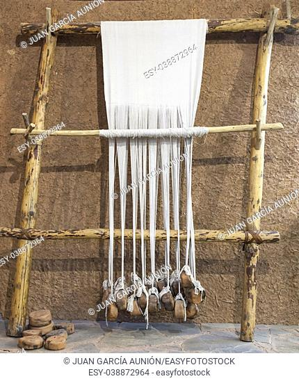 Reconstructed prehistoric age weaving loom. Mudwall ancient house replica
