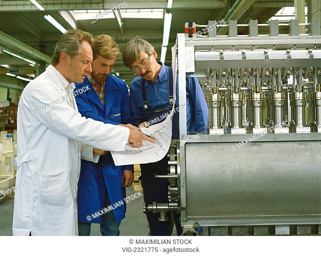 AssEMBLY OF A FILLING AND PACKAGING MACHINE FOR THE FOOD INDUSTRY. TECHNICIAN AND INDUSTRIAL MECHANIC DISCUssING A DESIGN DRAWING - 01/01/2010
