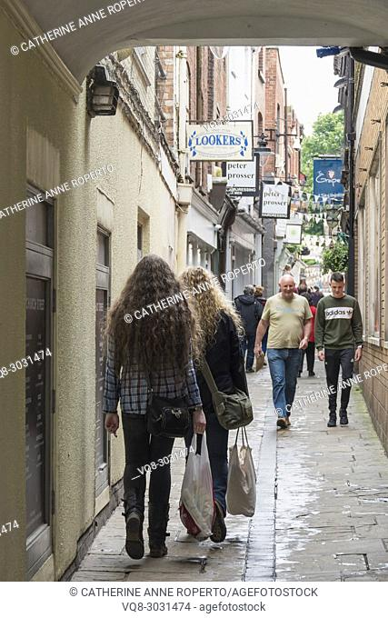 Girls with blonde and brown identical long curly hair walking through an arcade in Hereford's bunting filled artisan quarter, Hereford, England