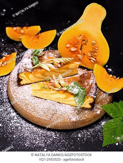 pumpkin pie on a wooden board and pieces of fresh pumpkin, black wooden background