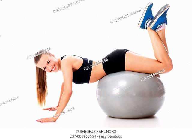 Beautiful and smiling woman doing abs exercises with fitness ball over white background