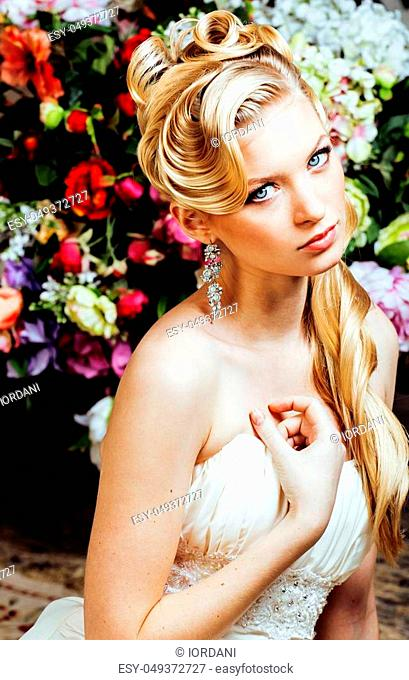 beauty young blond woman bride alone in luxury vintage interior with a lot of flowers close up