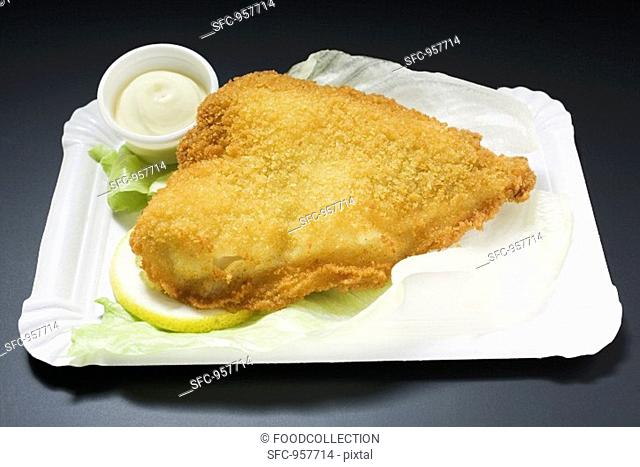 Breaded fish fillet with mayonnaise on paper plate