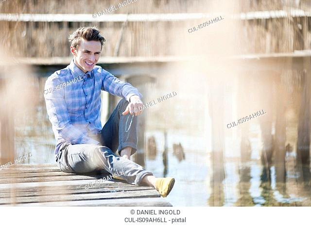 Mid adult man sitting on pier