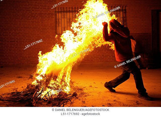 Young men jumping over a bonfire during San Antoni festival, Vilanova de L'Alcolea, Castellon, Spain