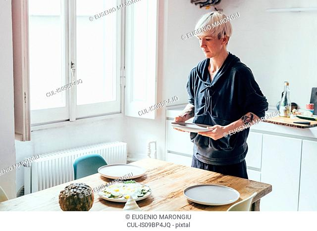 Woman setting table in kitchen