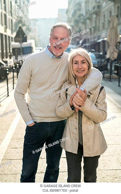 Senior couple hugging on street in city