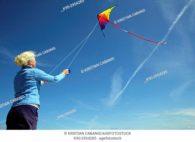 Young caucasian woman letting her kite fly with blue sky, Amrum, Northfrisian, Schleswig-Holstein, Germany, Europe